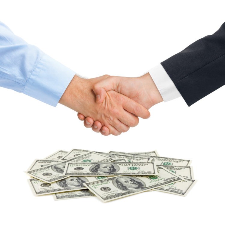 shaking hands over a pile of money